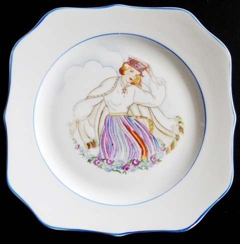Plate. The girl in folk costume with a flower garland